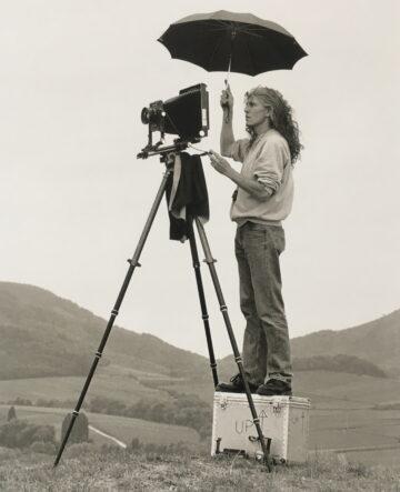 Der Fotograf Martin Blume steht auf einem Sockel an einem Kamerastativ und hält einen Schirm über sich. Schwarzweißfotografie.